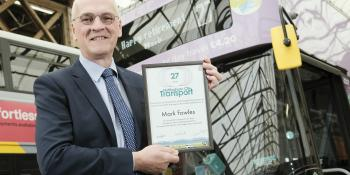 Mark Fowles holding his NCT long service award in front of an NCT bus